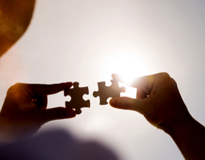 Woman hands connecting two jigsaw puzzle pieces against sunset sky.