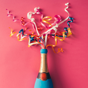 Champagne bottle with colorful party streamers on pink background. Flat lay