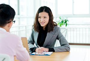 Businesswoman talking with visitor face to face at the table.