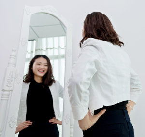 Attractive asian woman looking at her reflection in a mirror